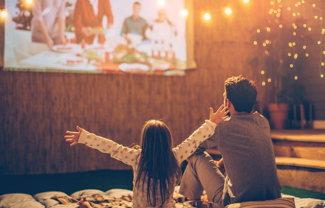 Image of child and adult watching family movie
