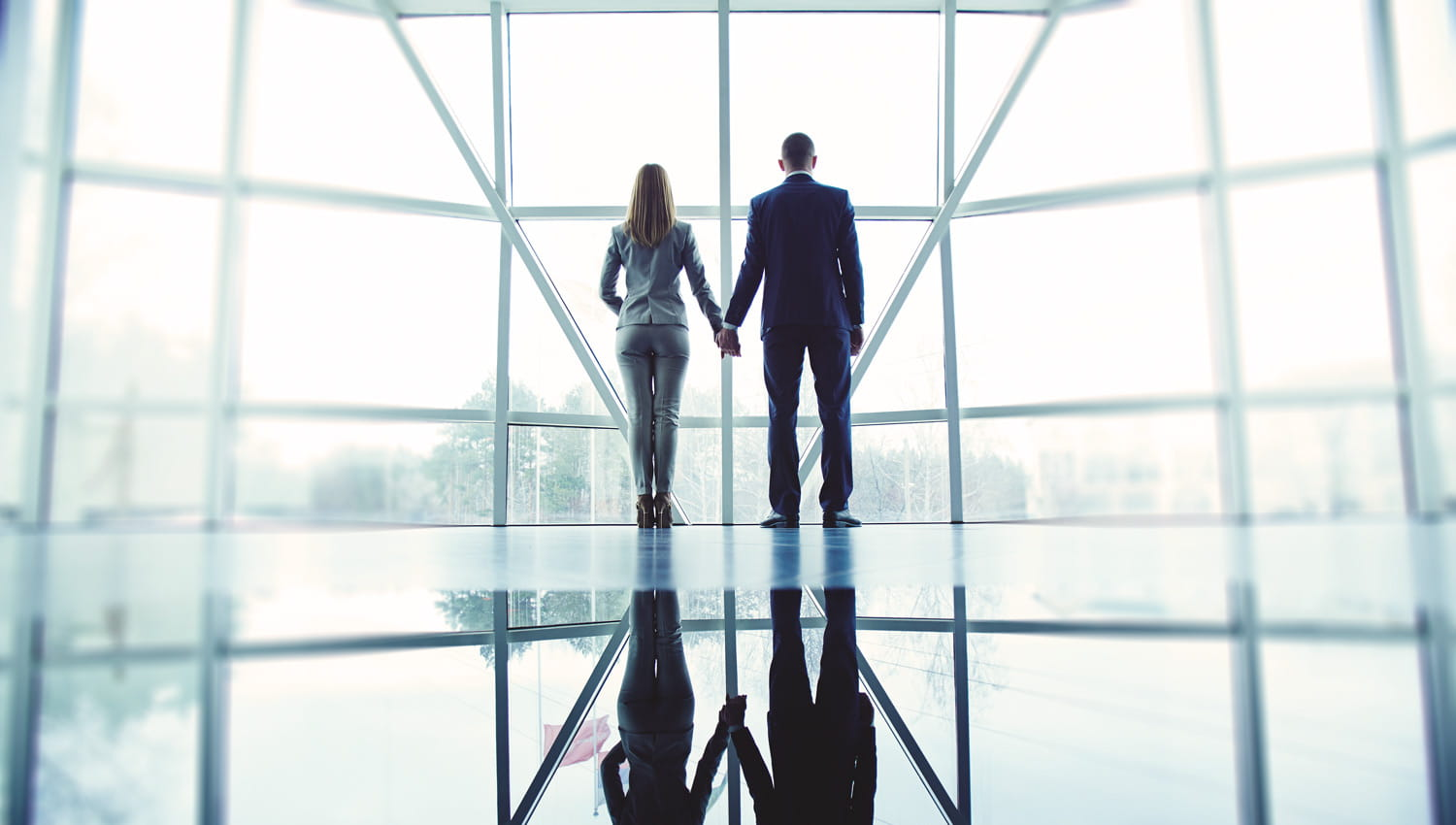 Couple standing in front of office window