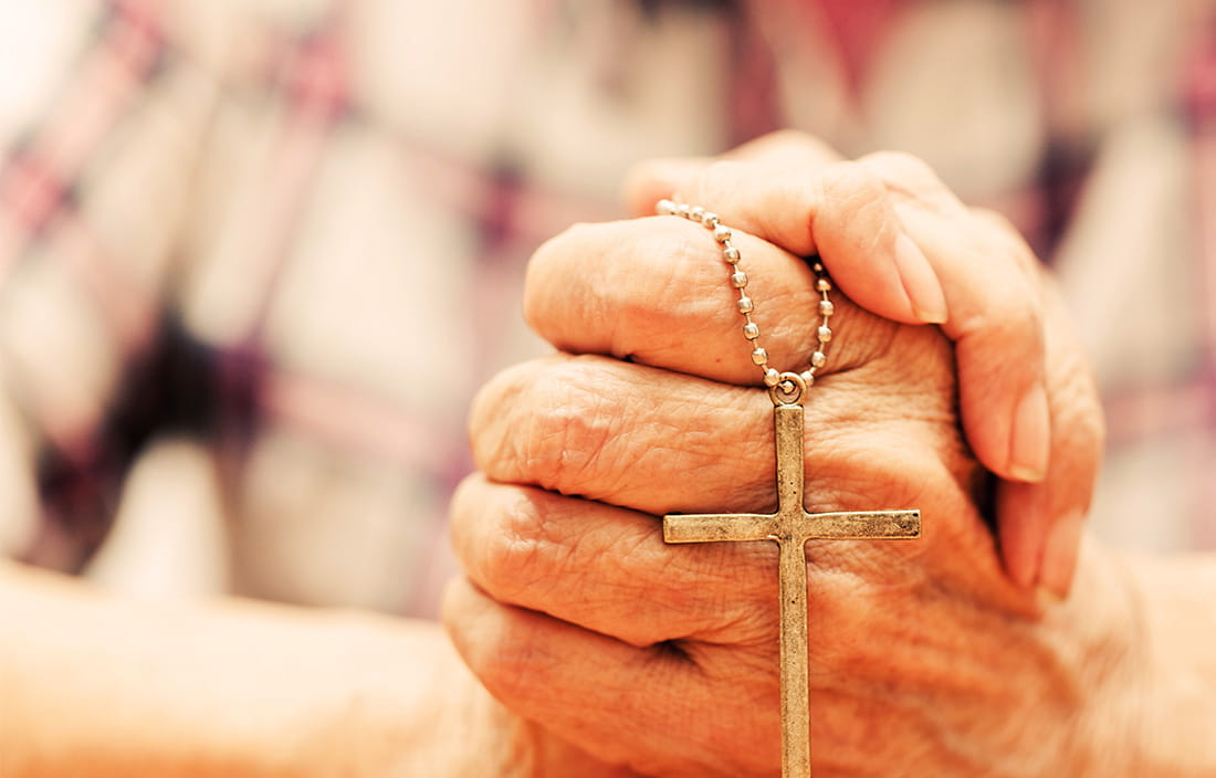 Image of a pair hands holding a cross