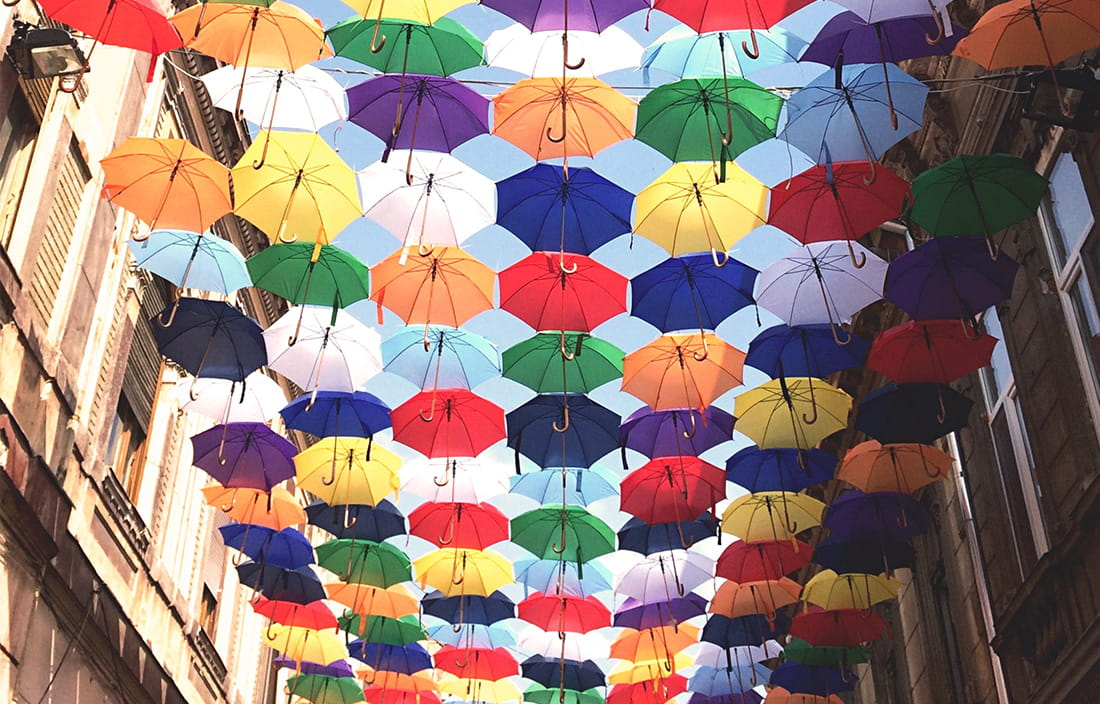 Image of umbrellas floating in air between two buildings