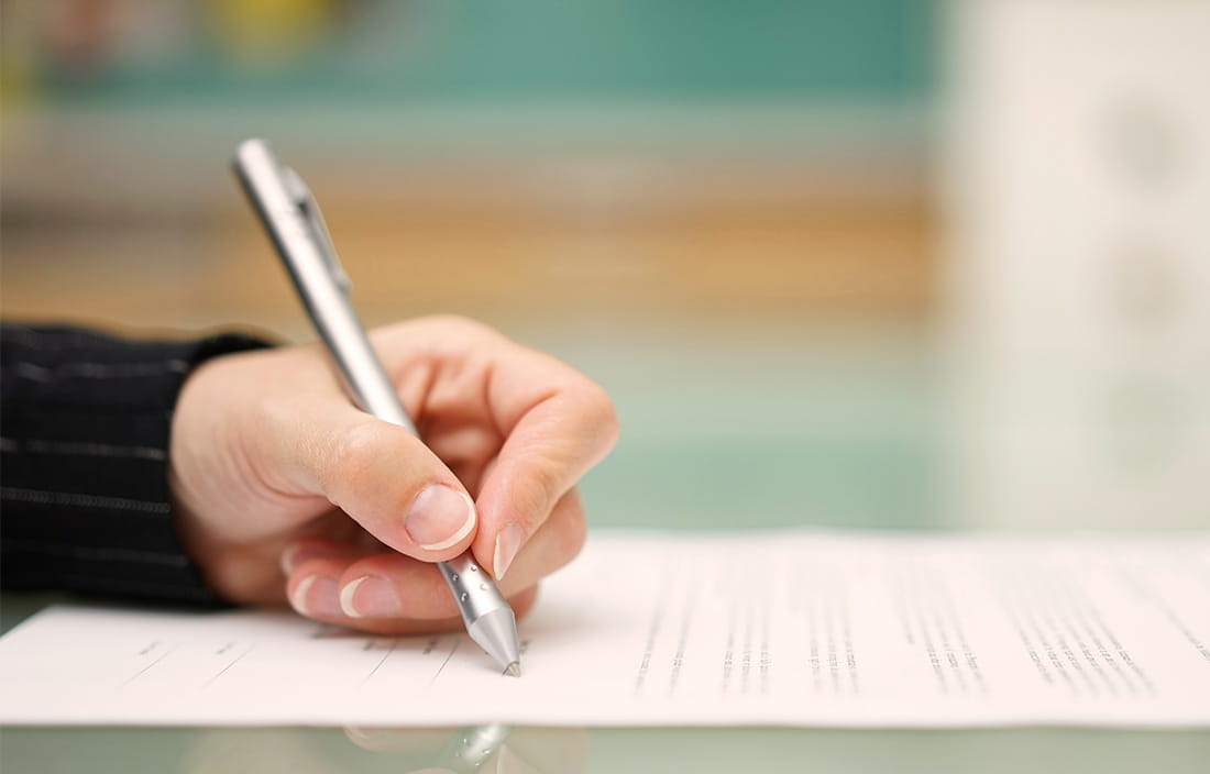 Image of a hand with a pen signing a document