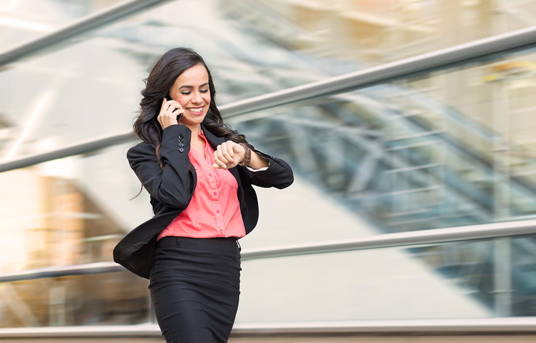 image of woman looking at her watch and talking on the phone while walking