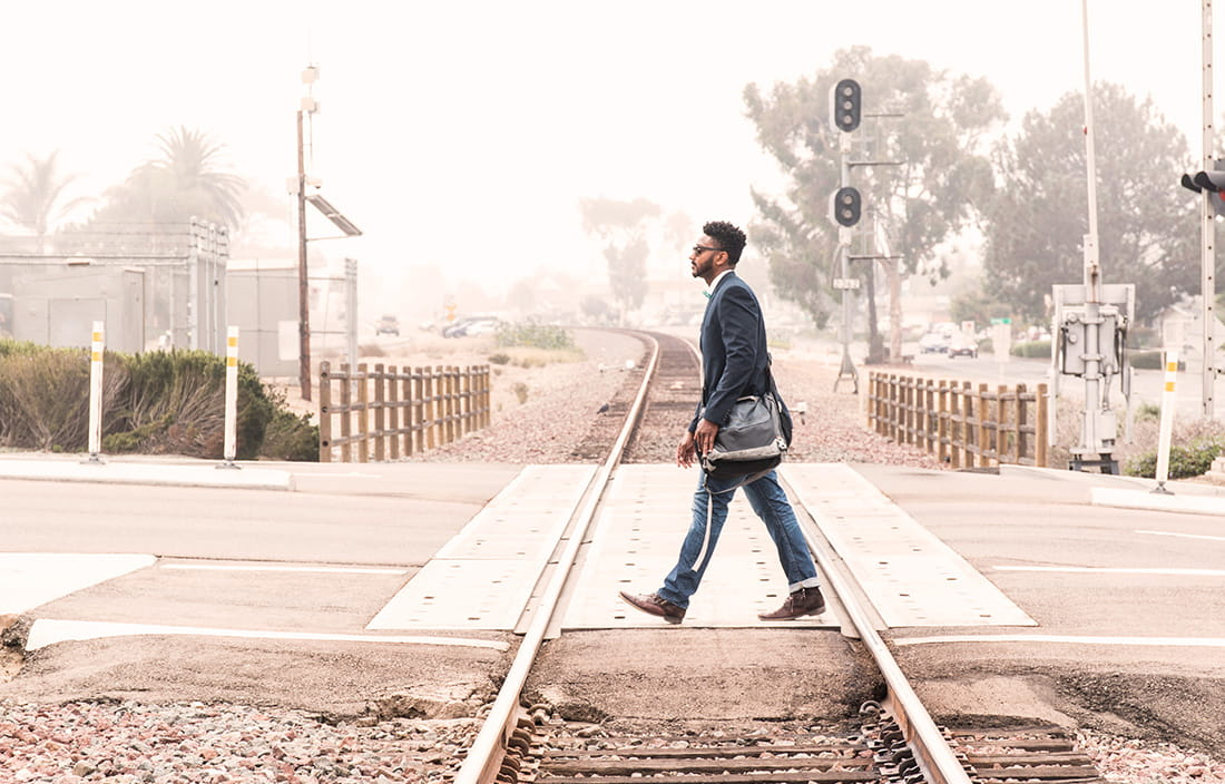 image of man crossing train tracks