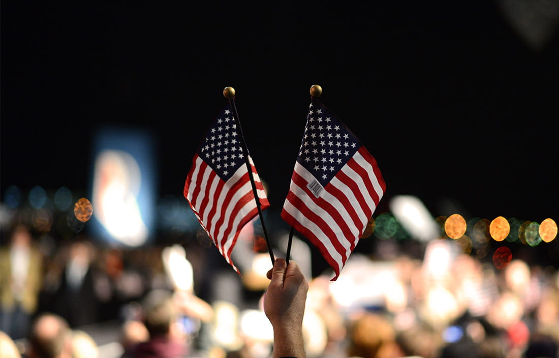 Image of person holding two american flags
