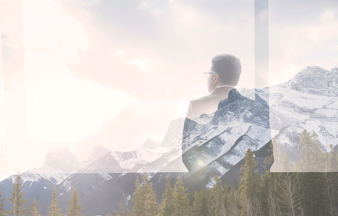 man looking out window at a mountain