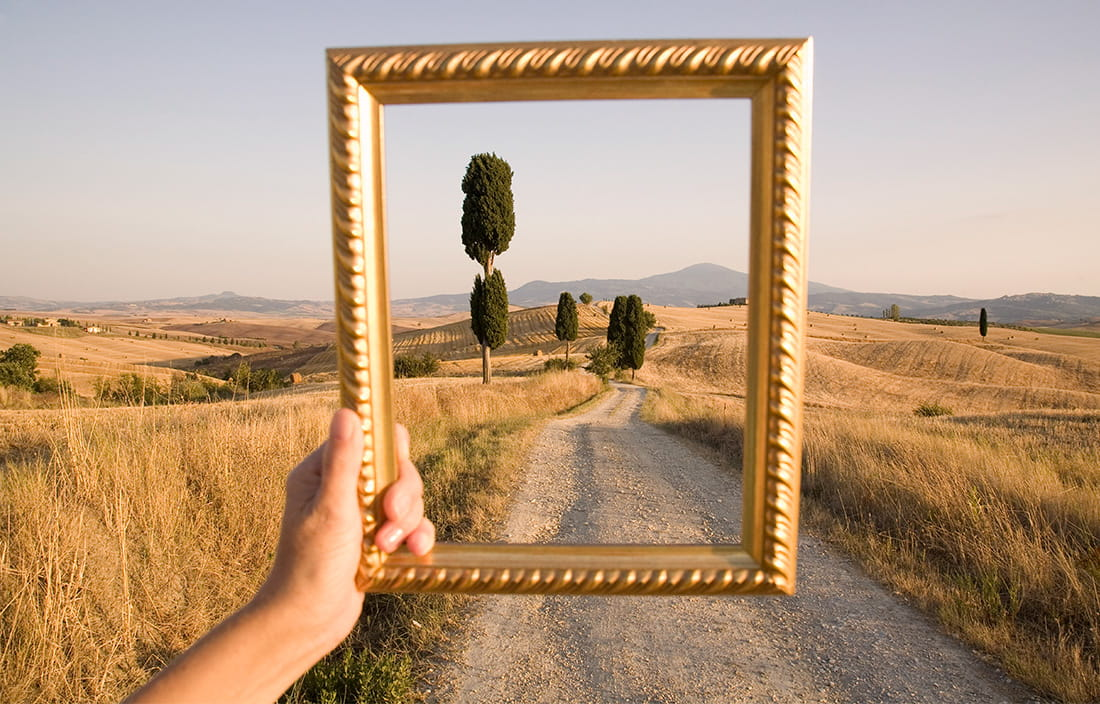 Holding up a picture frame to landscape
