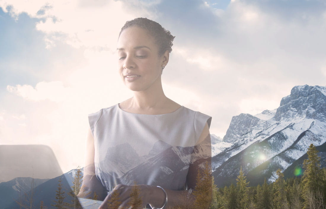 Woman working on laptop, superimposed over a mountain scene.