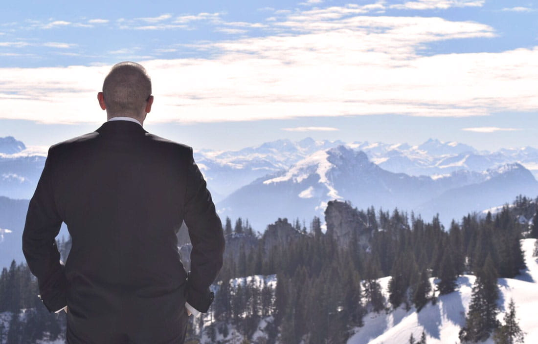 Man in suit gazing out over a snowy mountain landscape.