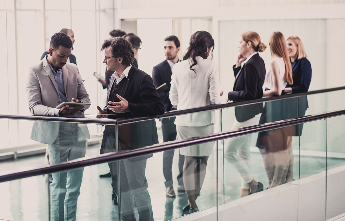 A group of business people leaning against a glass railing.