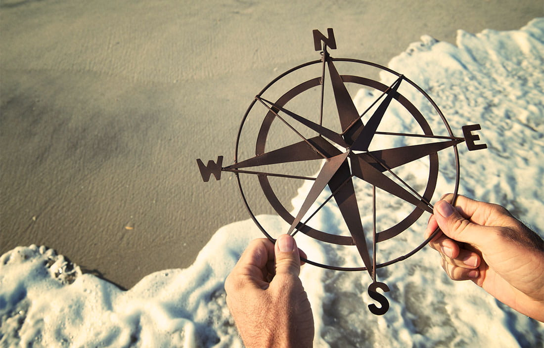 Hands holding a compass at the beach