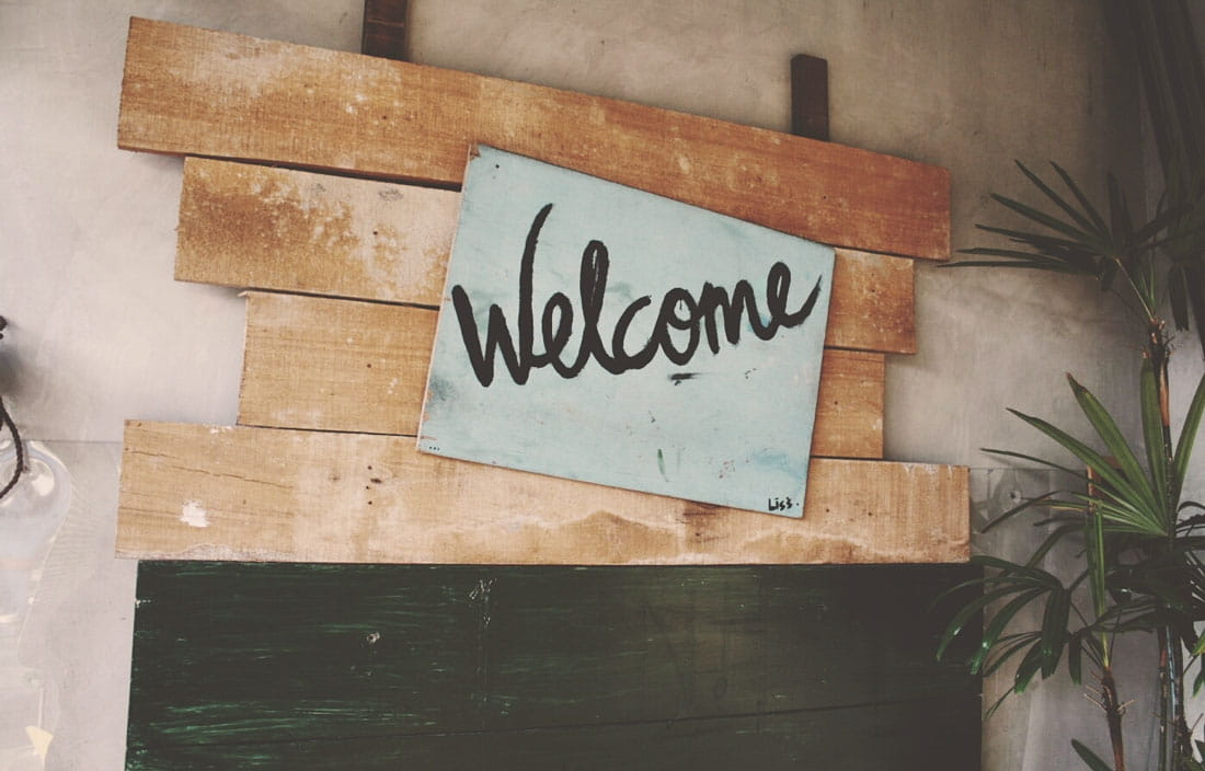 "Image of handwritten ""Welcome"" on natural wood boards"