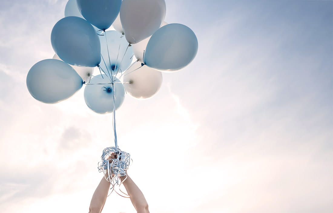 An image of hands holding balloons