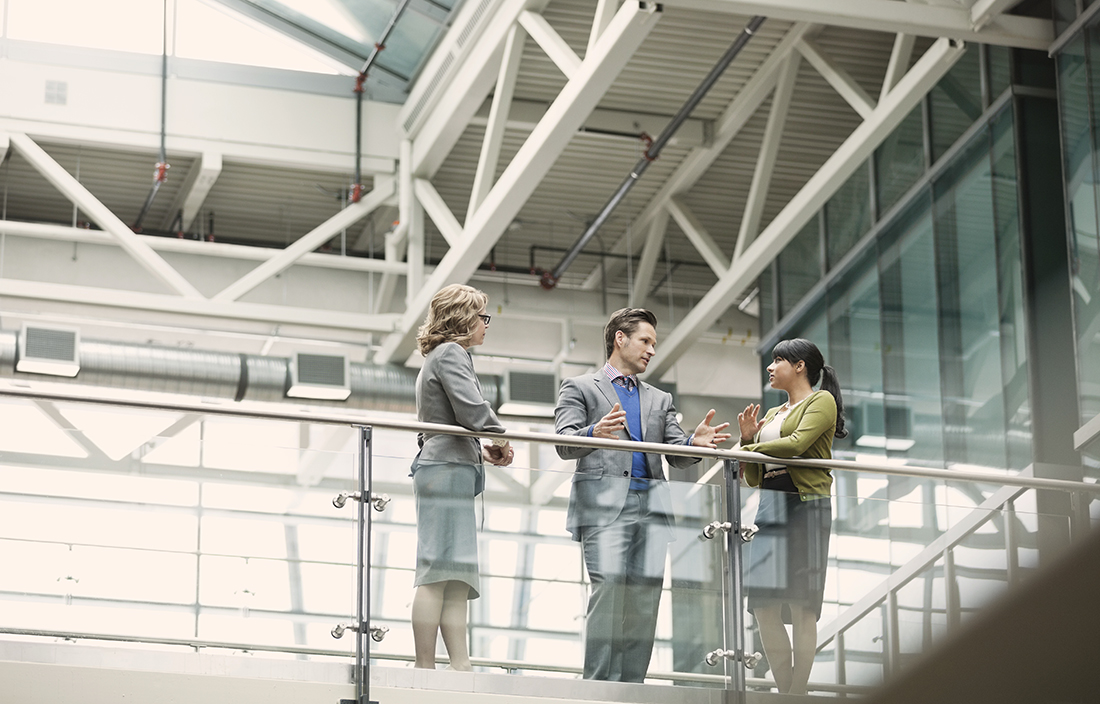 Three business people talking on walkway, along glass railing.