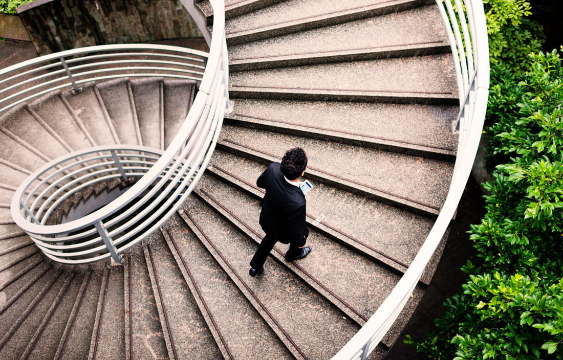 Image of man walking up outdoor spiral staircase.