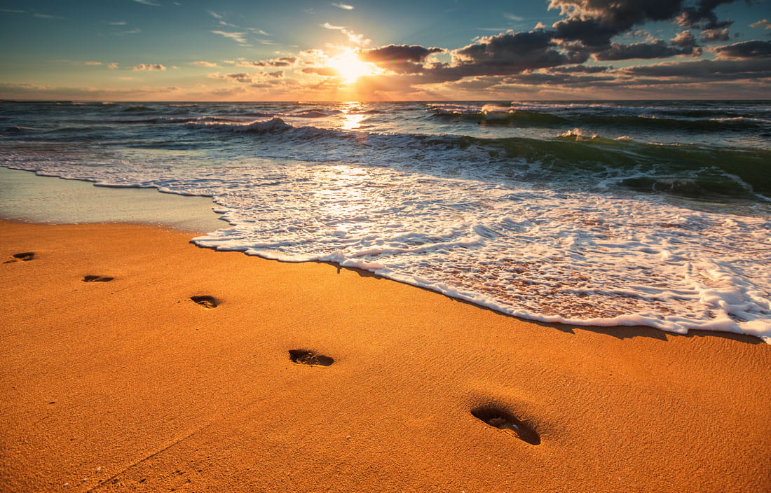 Footsteps on the beach at sunset.