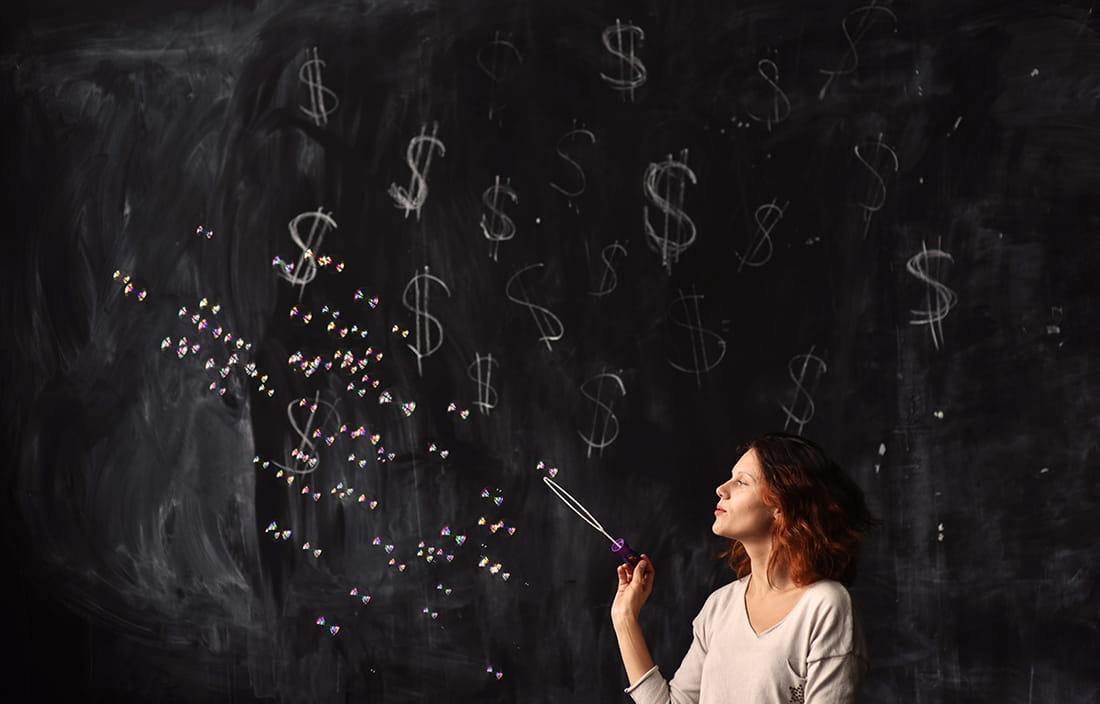 Image of woman blowing bubbles in front of chalk board with dollar signs