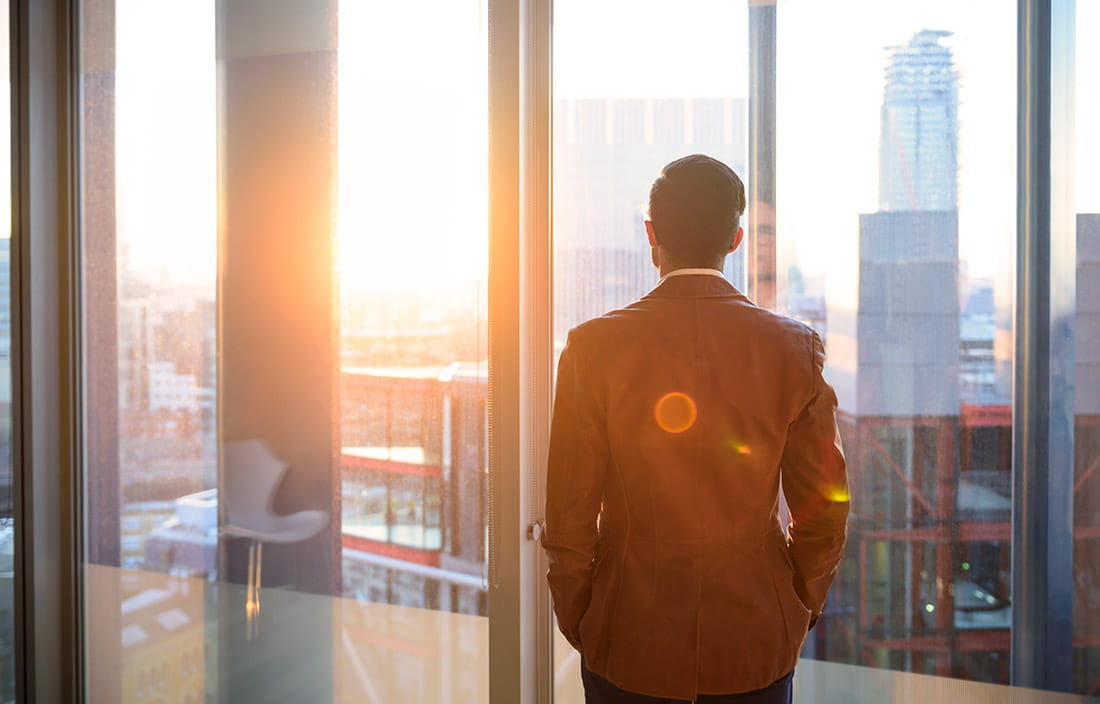Businessman watching the sunrise from his office window