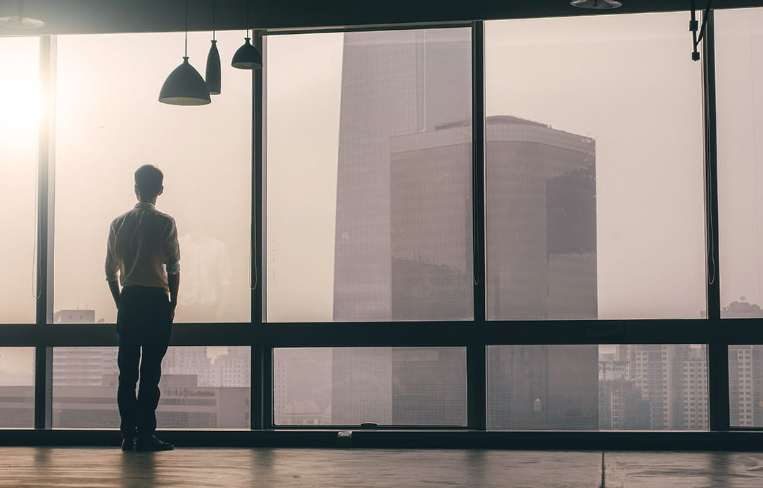 Image of man standing in front of windows looking at corporate buildings
