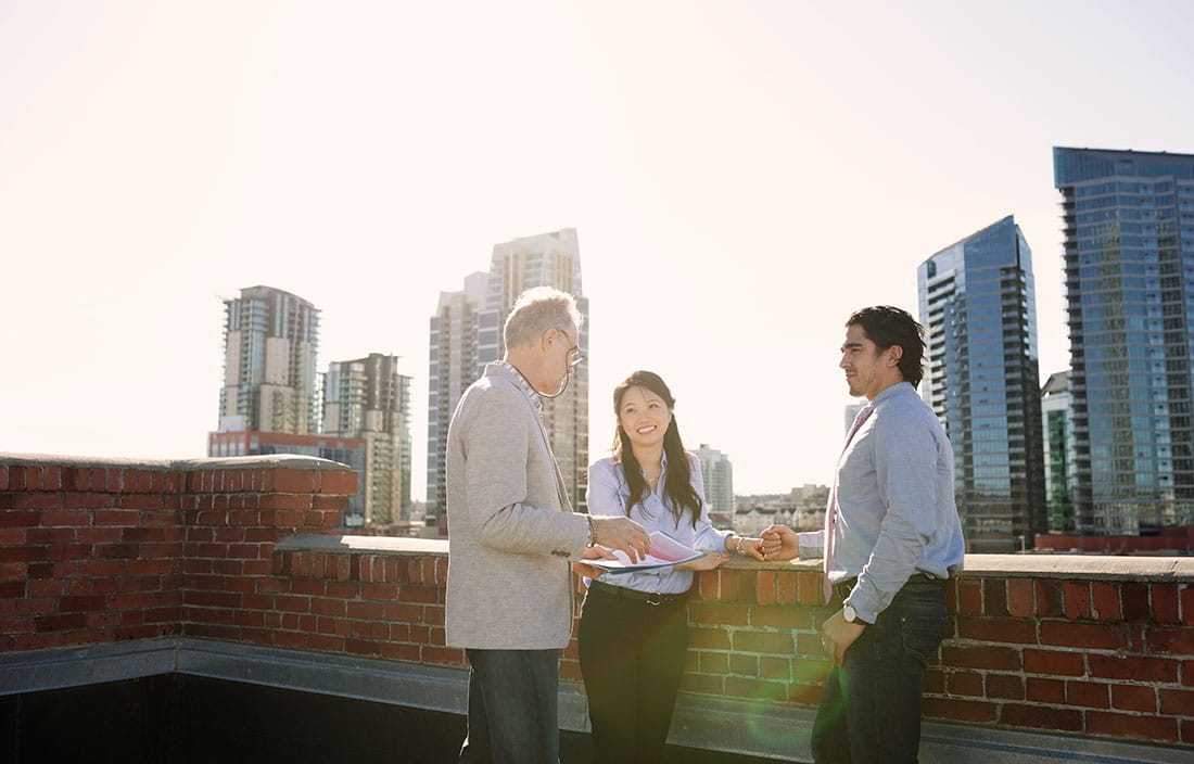 Image of diverse group holding meeting on rooftop