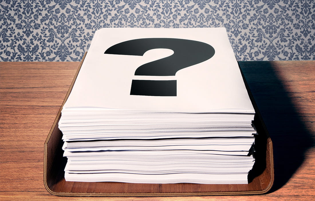 Image of a stack of papers with a question mark on top