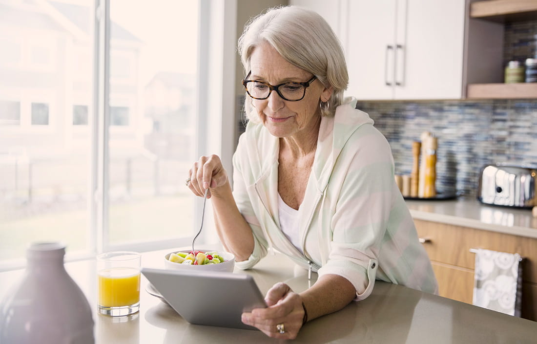 Woman eating breakfast and looking at her tablet