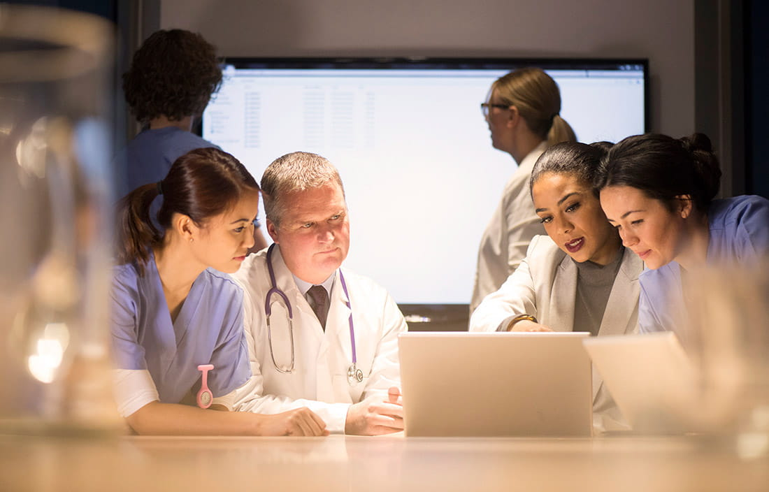 Healthcare providers review data on a laptop