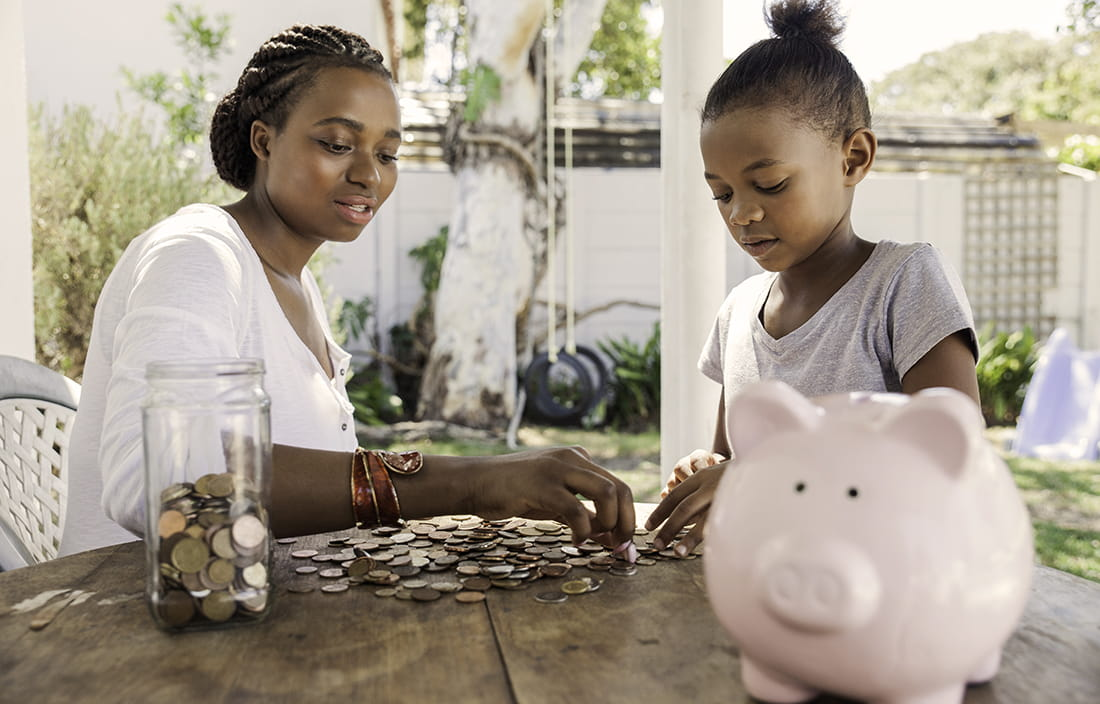 Image of mother and daughter counting coins from piggy bank