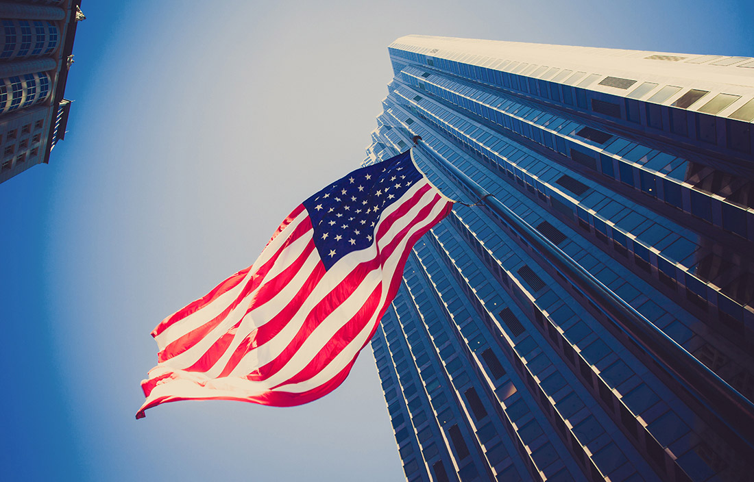 Picture looking up at an American flag waving in front of a skyscraper.