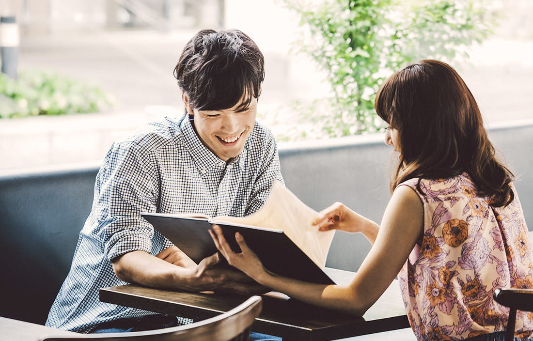 Man and woman sitting at a table while looking at a book and laughing