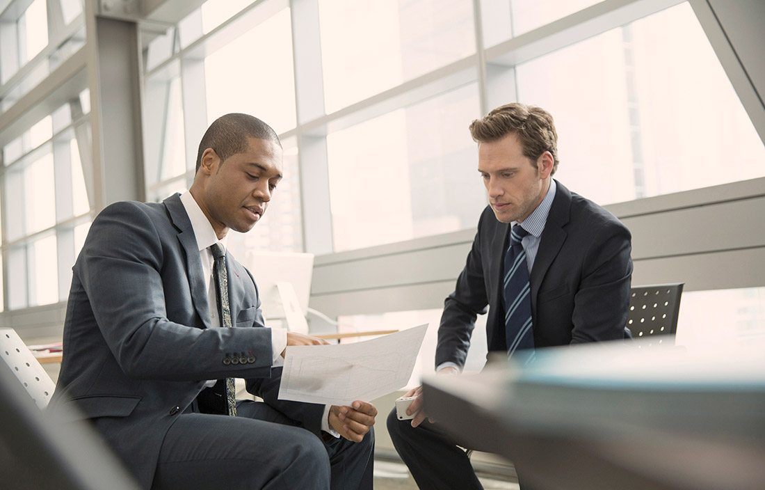 Two men in suits sitting and go over paperwork