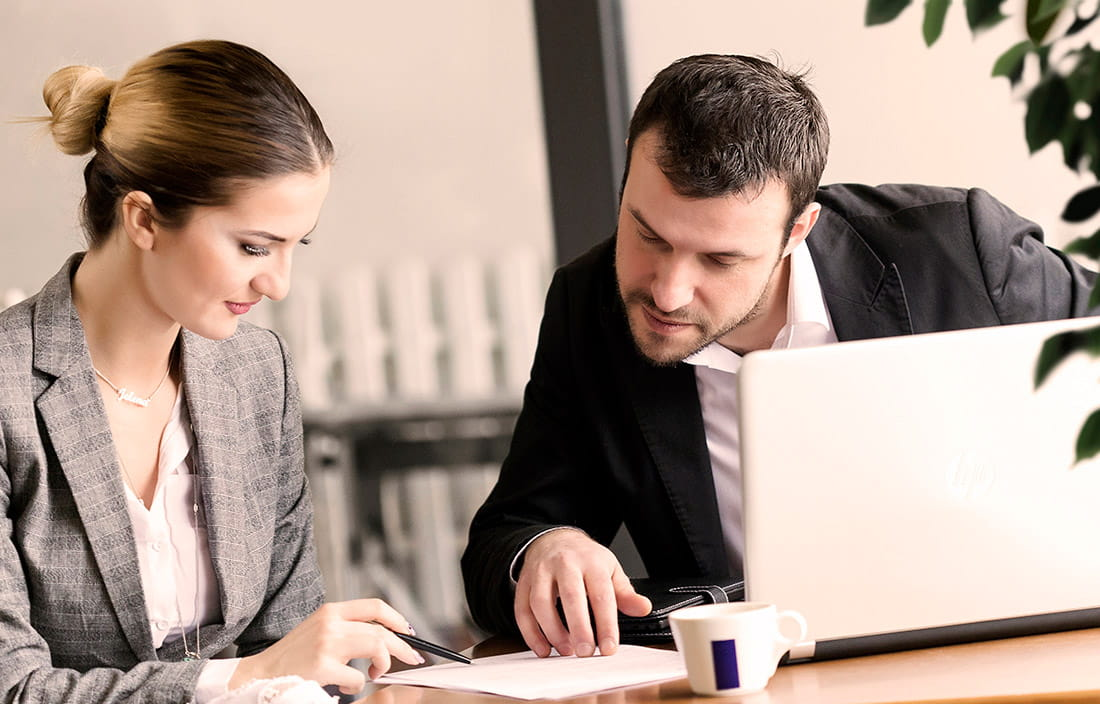 Man and woman going over paperwork at a table with a laptop