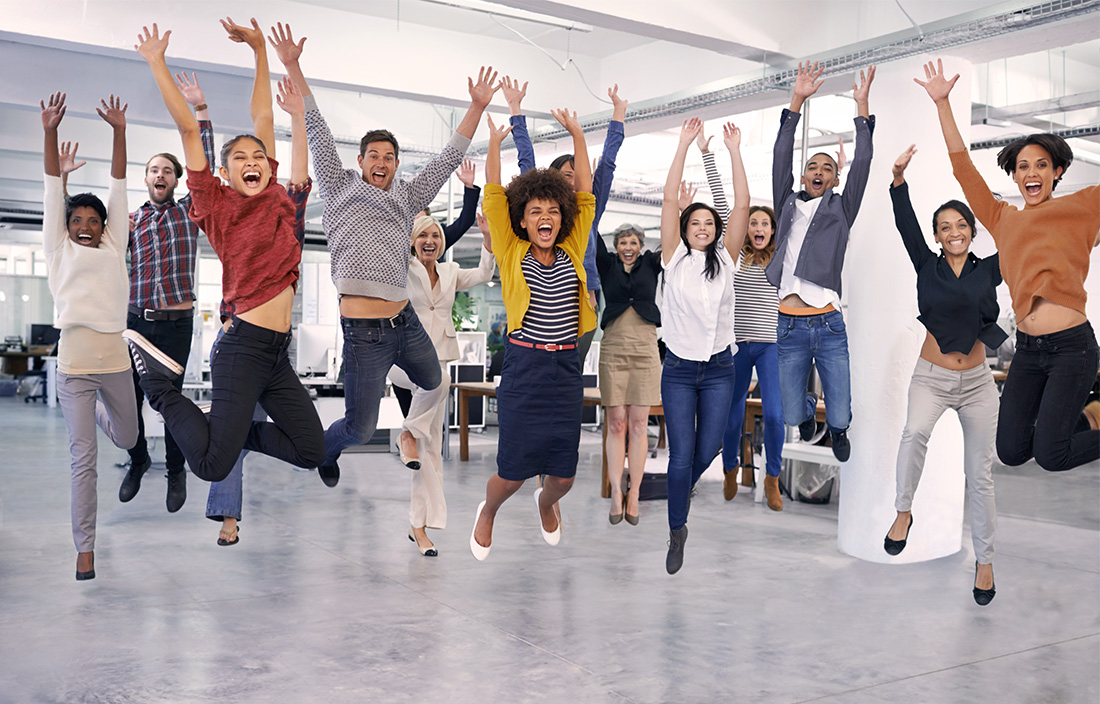Image of young people jumping in an office environment