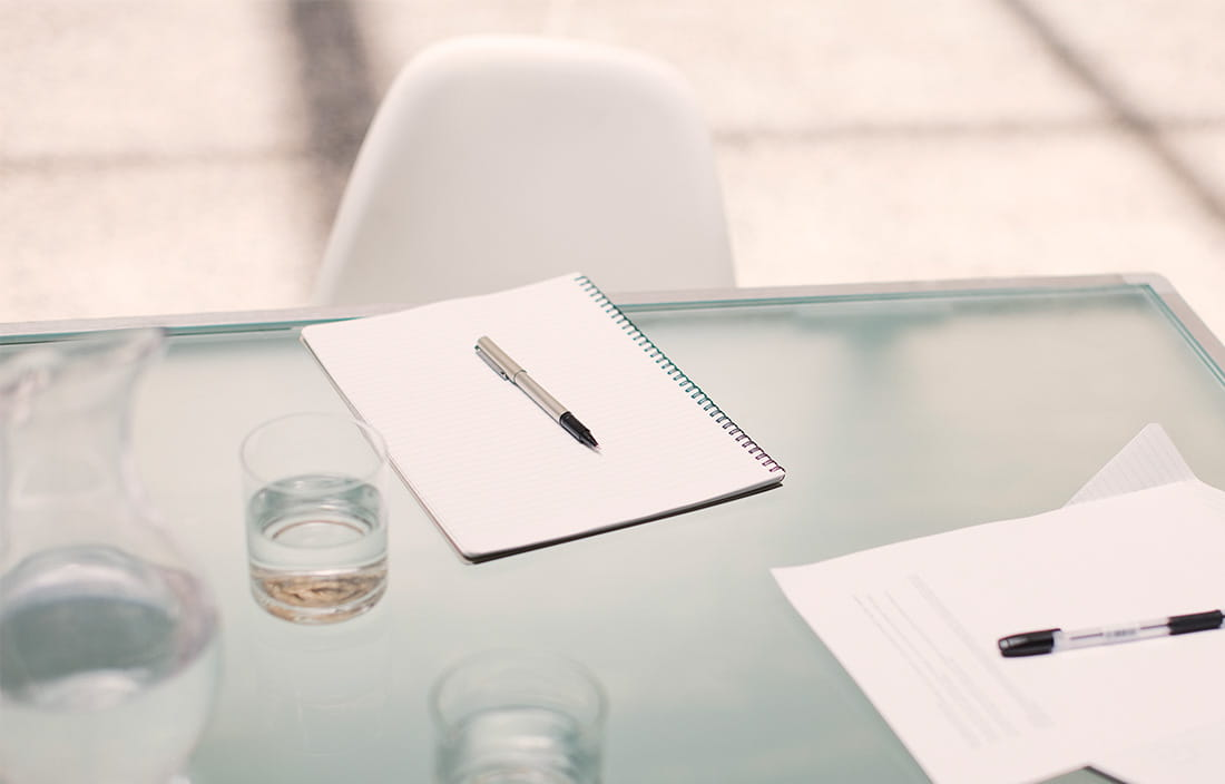 Image of a desk with paper and pen