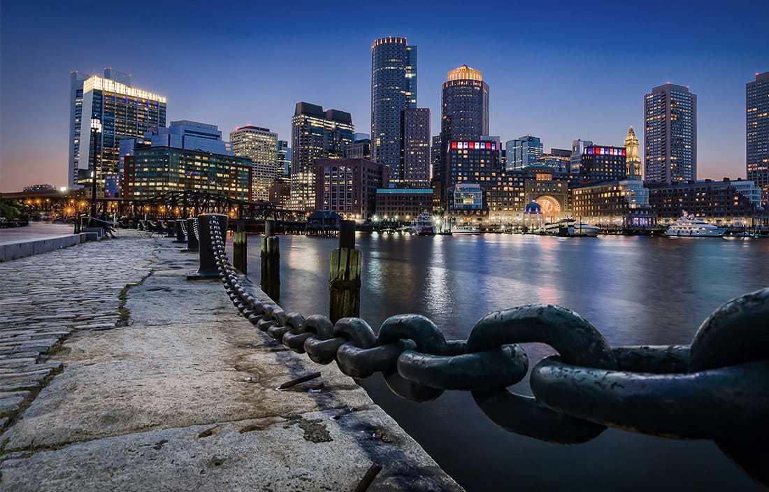 pier in Boston at night with the city skyline in the background