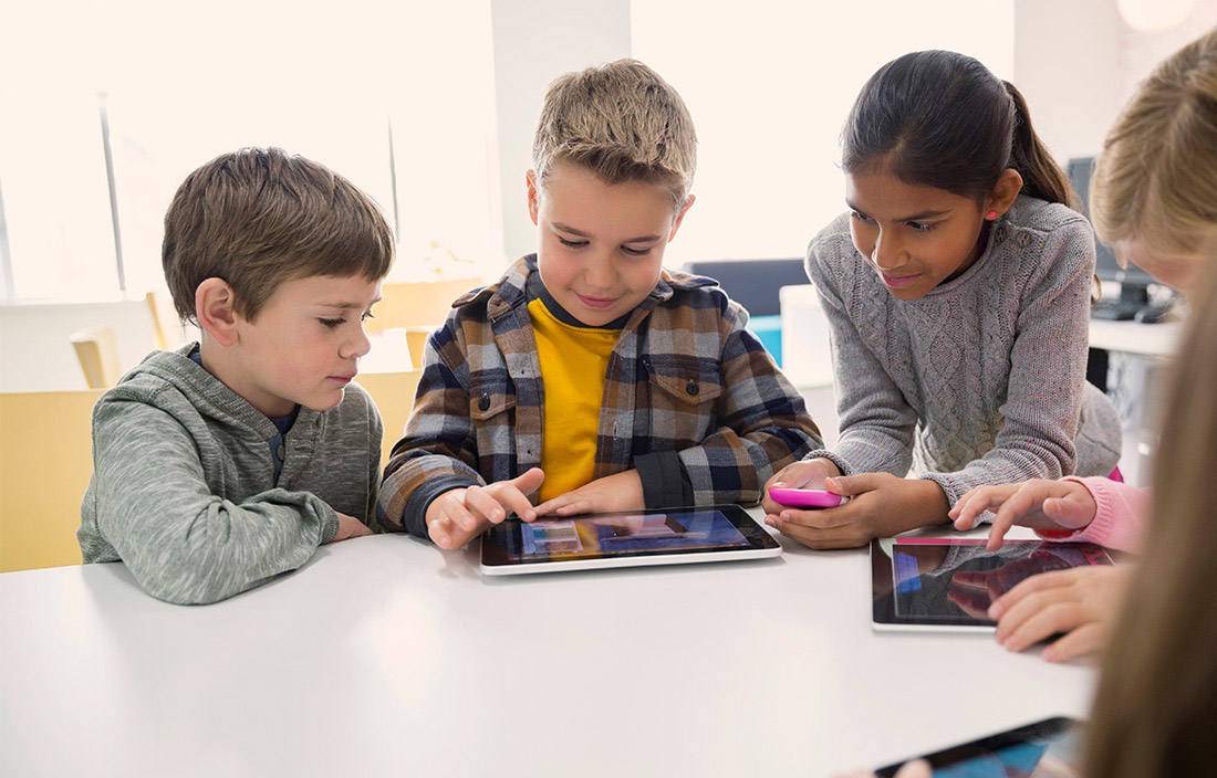 small group of kids at a school table looking a tablet device