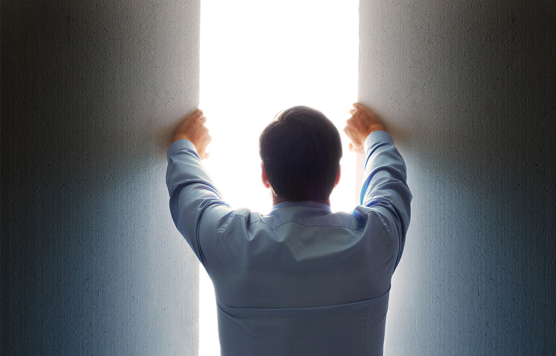 business man opening opening nondescript panels to let in bright light
