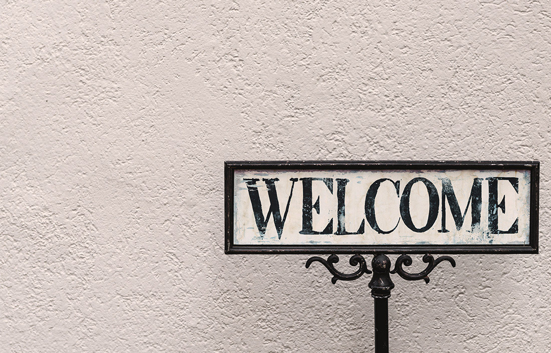 antique welcome sign against textured white wall