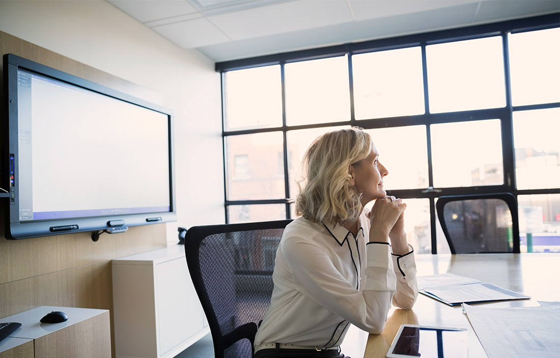 Image of woman sitting at a desk and looking out of a window