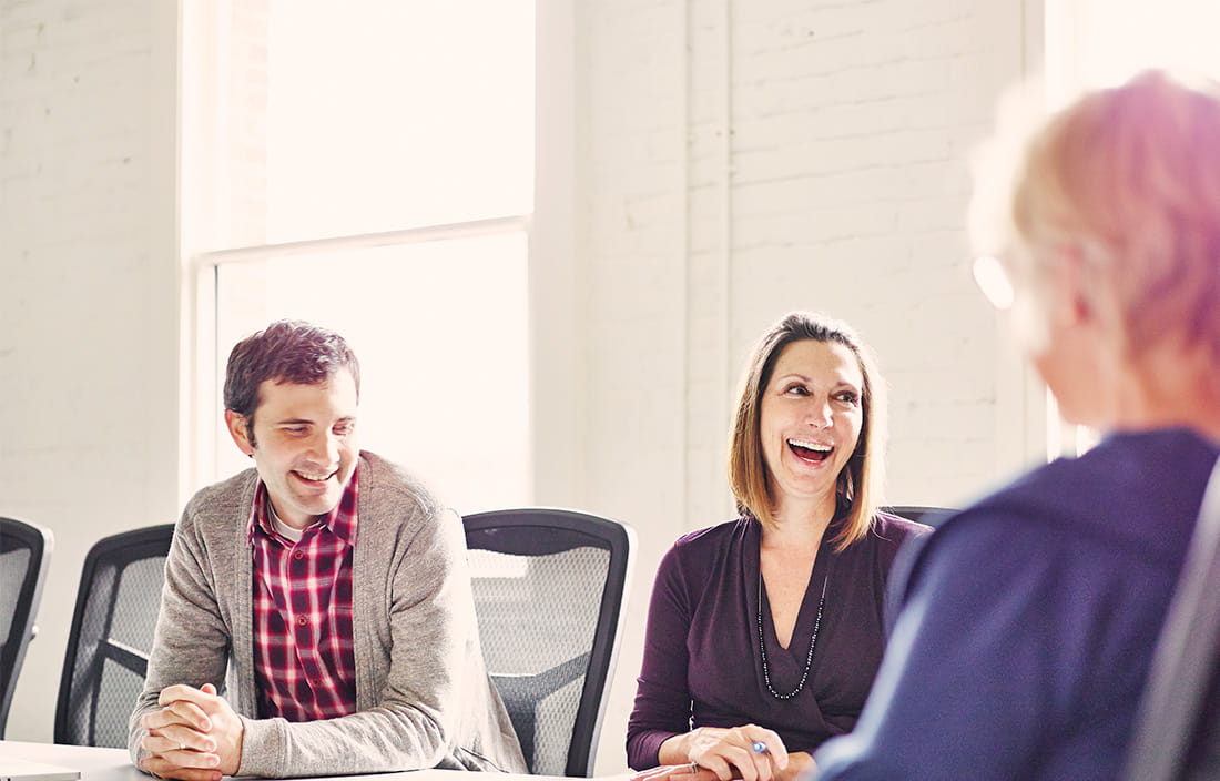 Image of people laughing during a meeting