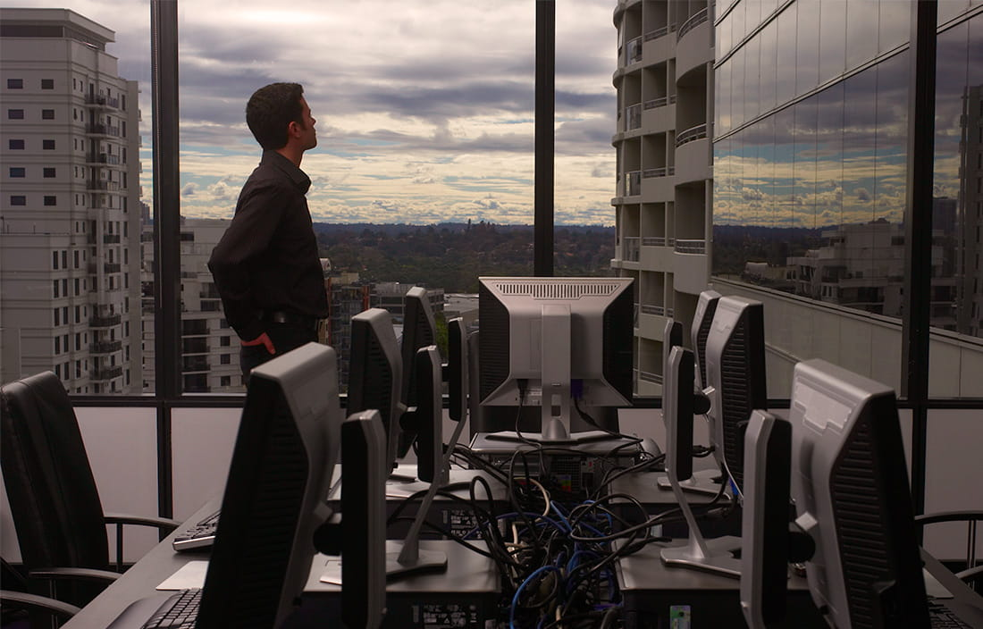 Image of man looking out window of an office building