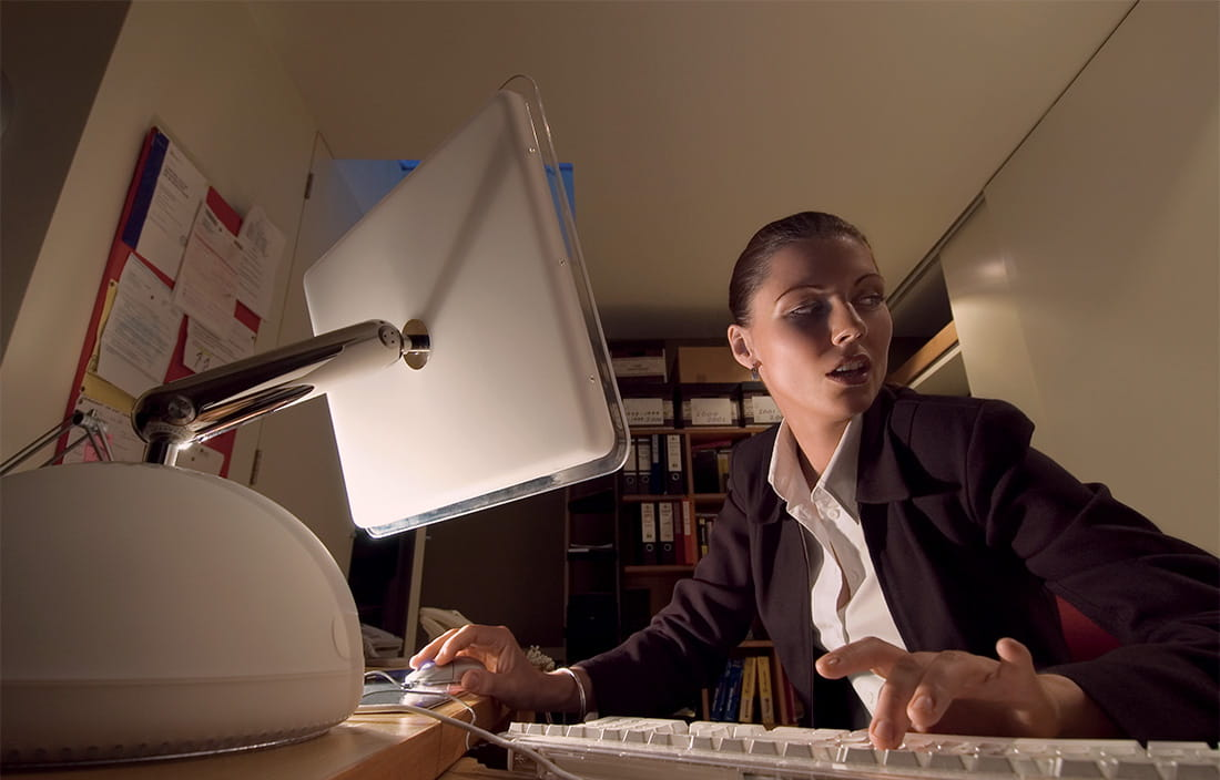Image of woman on computer in dimly lit room