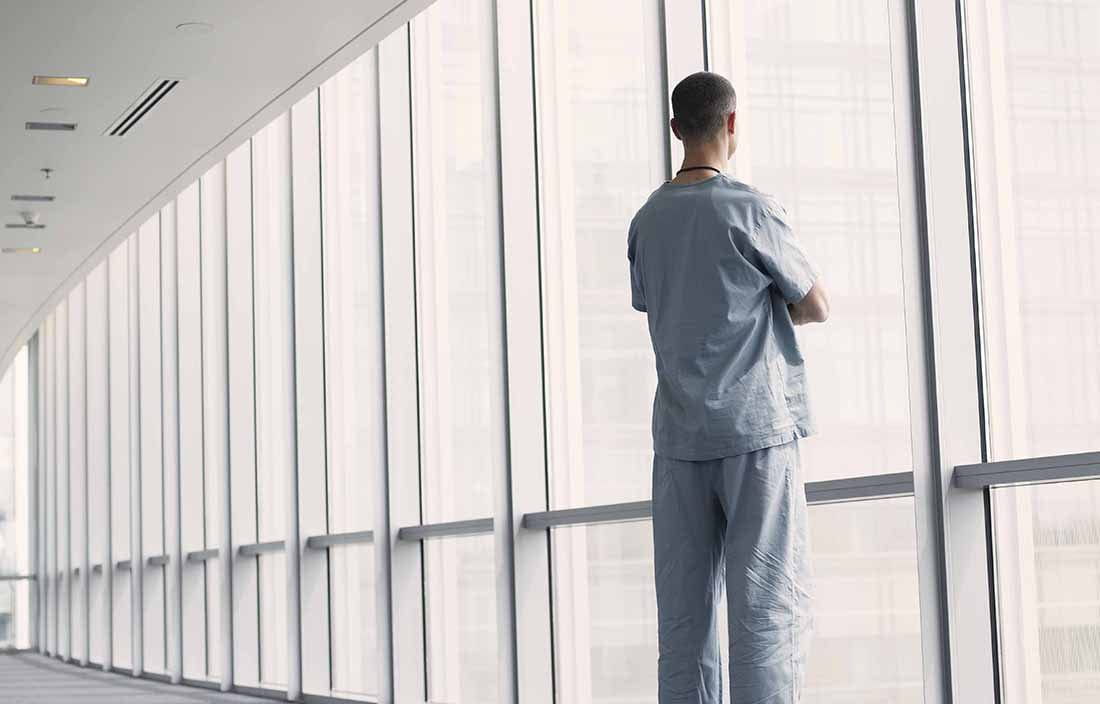 Doctor standing in a walkway looking out the window.