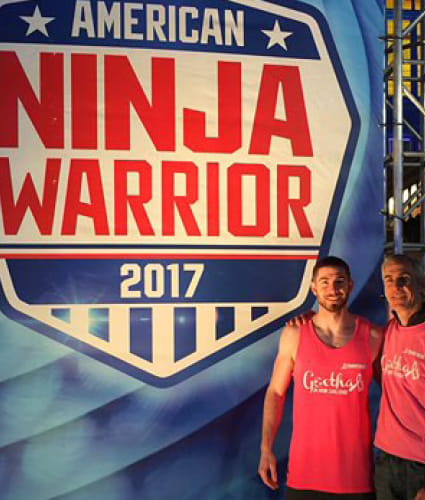 Matt Goethals in front of the American Ninja Warrior sign with his dad.