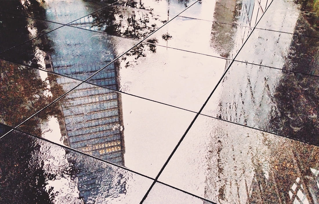 Reflection of skyscraper on wet pavers