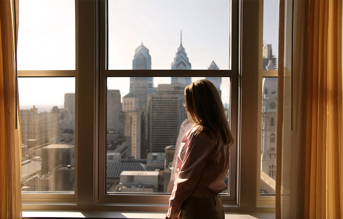 Woman viewing city through window