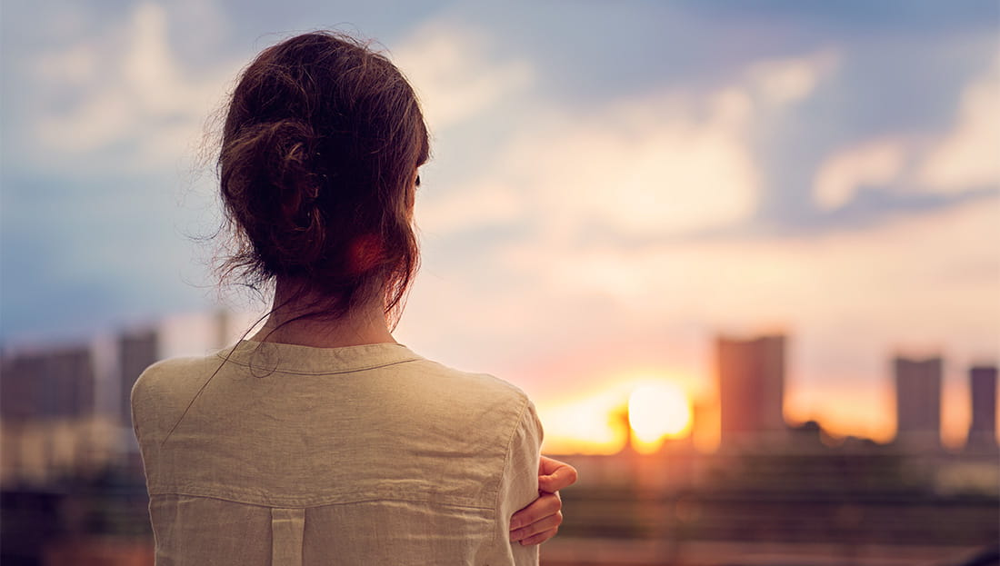Woman watching the sunset over a cityscape
