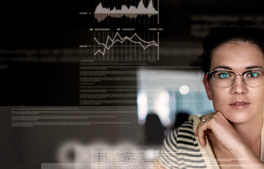 woman with glasses looking at technology