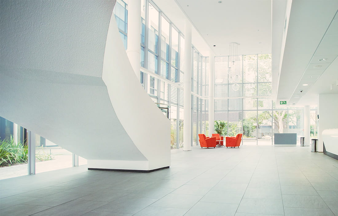 modern multi-level white office lobby with two red seats in the distance