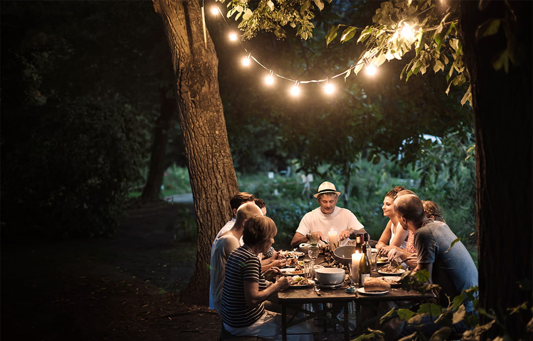 Outdoor dinner with friends and family at night in backyard. string lights frame the shot and add light to the table