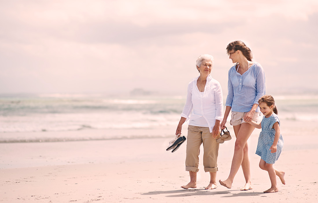 grandmother, mother and child walk together on the beach